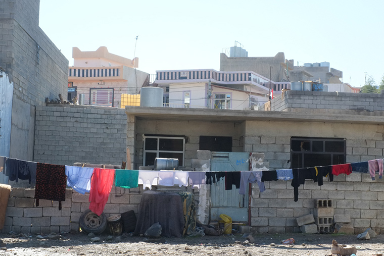 Laundry hangs in front of an unfinished, concrete block house in Kurdistan. Many of these unfinished houses have become homes to refugees from Syria and Iraqi families displaced by ISIS.