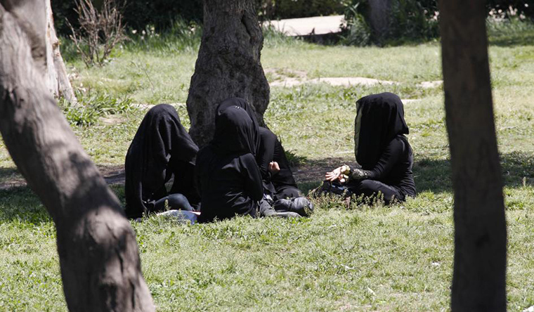 A small group of women sit in a circle in a park. They are dressed in black, with only their hands exposed.