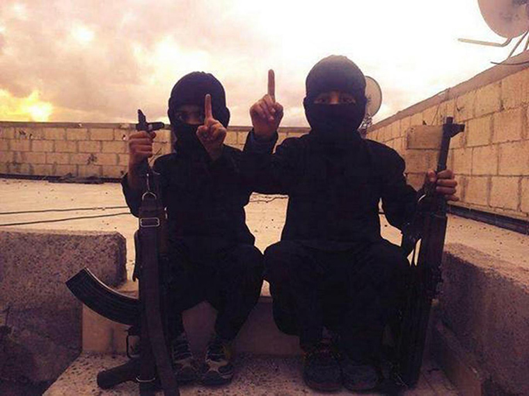 Two women pose, dressed in black and holding guns. Only their eyes are showing. They are committed to the cause of ISIS.