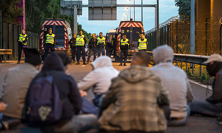 French police prevent refugees from reaching France at the Calais crossing.