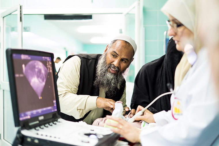 A pediatric cardiologist based in eastern Libya, checks a patient's heart.