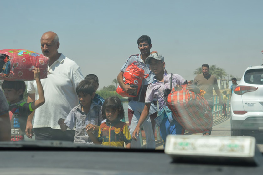 Families fleeing ISIS carry what they can as they try to find safety.