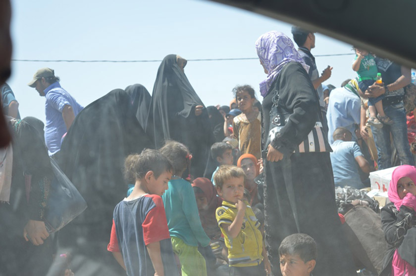 Families displaced by ISIS wait their turn to cross the bridge as they flee.