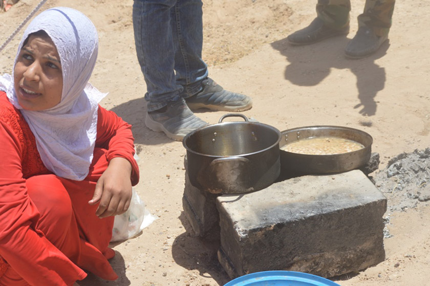 A woman displaced by ISIS tries to cook for her family on a makeshift stove built of cinder blocks.