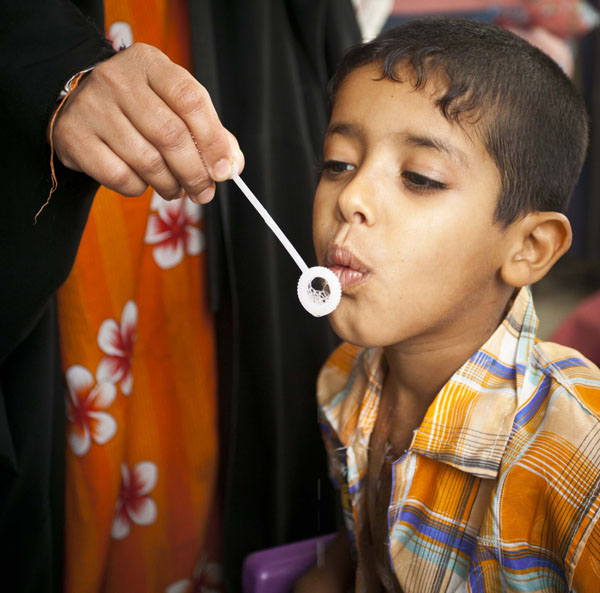 Moustafa, a young Iraqi boy, blows bubbles to strengthen his lungs after a life-saving heart surgery