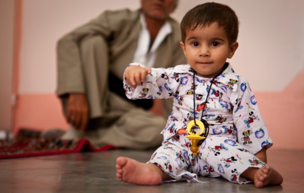 An Iraqi 1-year-old plays on his family's floor months after having life-saving heart surgery