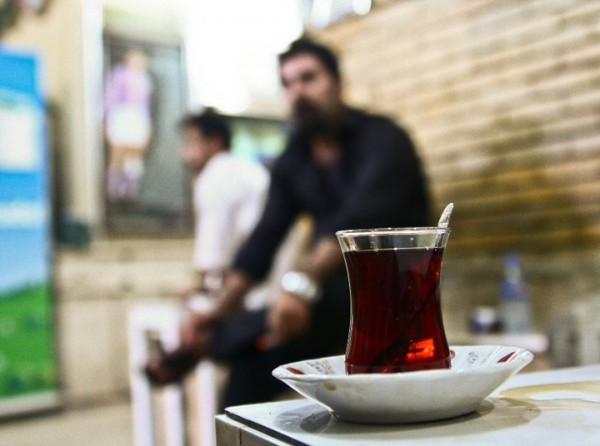 A man sits and takes in the sights and sounds of an Iraqi tea shop.