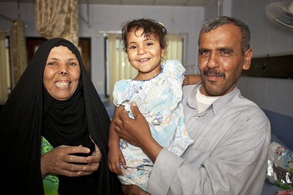 Roqoia and her parents flash big smiles for the camera.