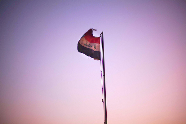An Iraqi flag waves in the sky during a beautiful Iraqi sunset.