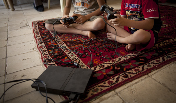 2 Kurdish boys playing playstation 2 in Iraqi Kurdistan.