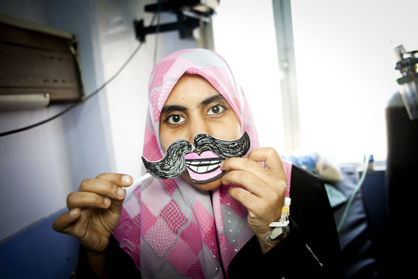 An Iraqi girl shows off her smiley-face and mustache for the camera.
