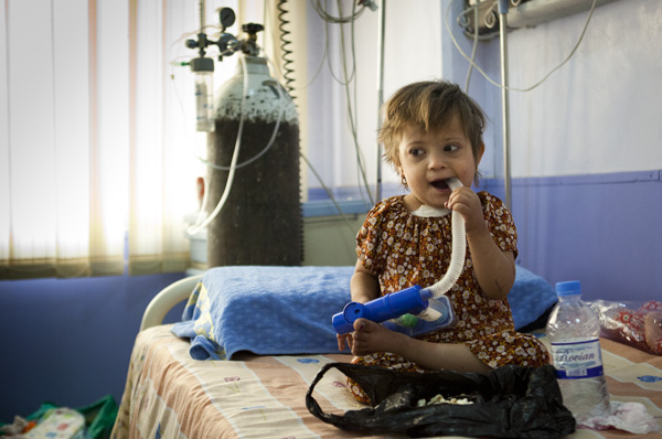 Noor, a young Iraqi girl, chews on hospital equipment after a successful heart surgery!