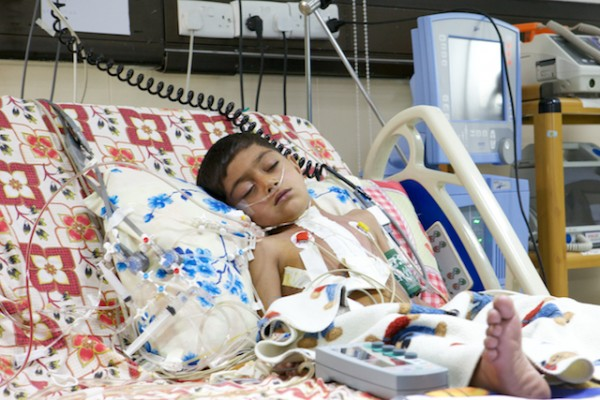 A photo of Amjad resting up in ICU after his heart surgery.