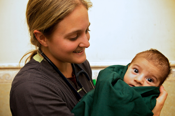 A photo of a partner nurse holding an Iraqi baby.