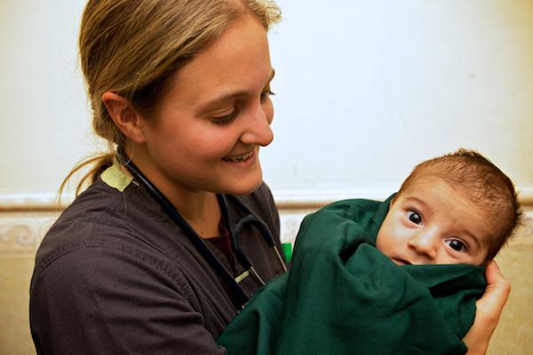 A photo of a partner nurse holding an Iraqi baby.