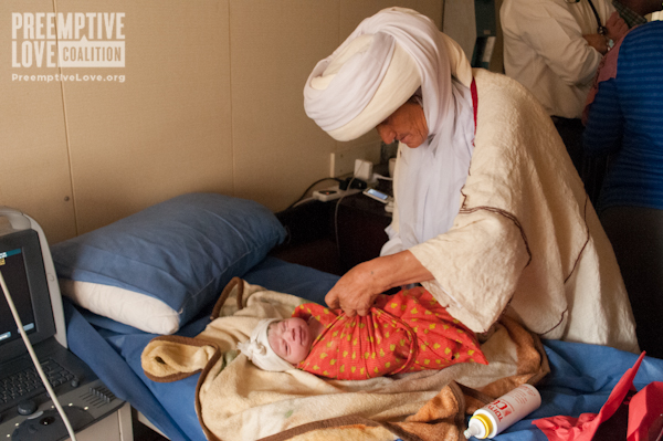 A Yazidi Grandmother wraps her baby