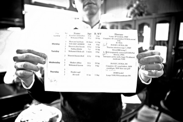 A photo of Jeremy Courtney holding up a surgery schedule/plan.