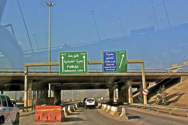 A photo of road signs pointing to Fallujah on the road from Baghdad to Anbar Province.