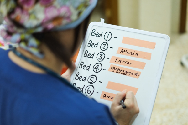 A photo of an ICU nurse taking note of the patient list.