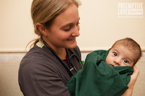 A happy nurse holds a new baby.