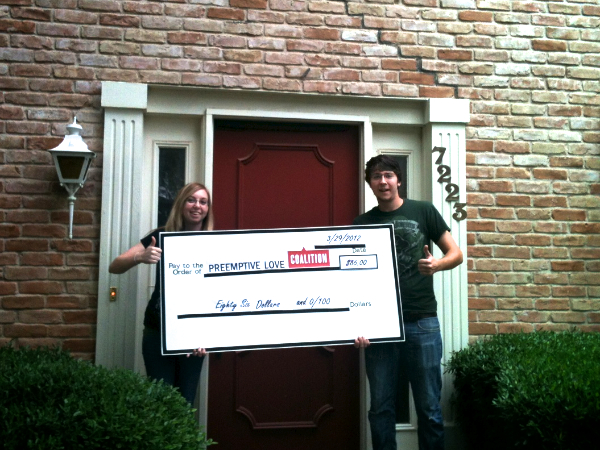 A photo of Matt & Devin holding a check for PLC in front of their new house!