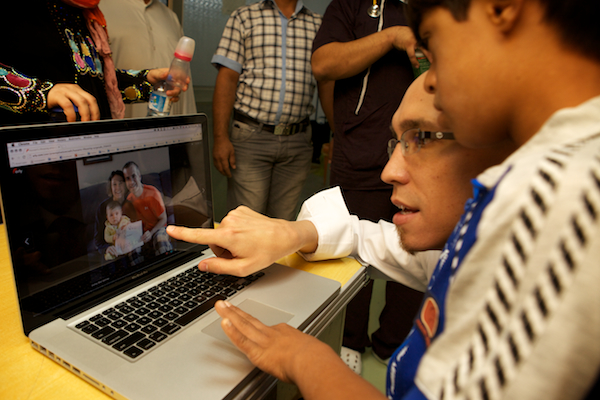 A photo of Jeremy Courtney showing Hussain the photos on his personal support page.