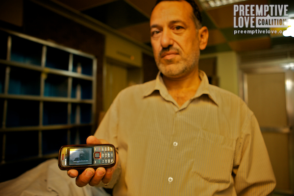 A photo of Nassir's father showing off his son's surgery video on his cell phone.