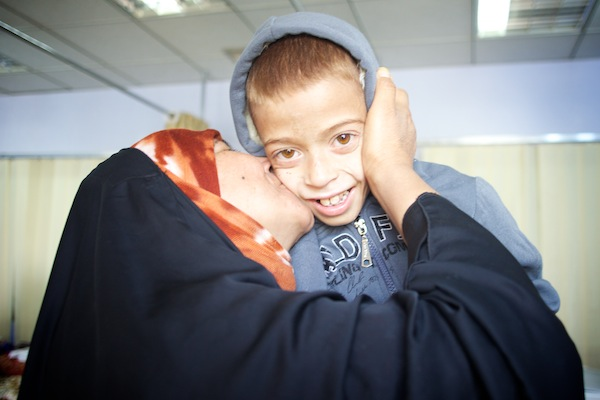 An Iraqi mother kissing her son on the cheek.