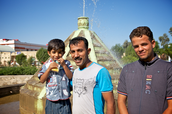 A photo of Hassin with his father and cousin in front of a fountain on the hospital grounds.