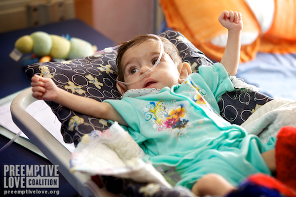 A photo of an Iraqi baby girl holding both fists in the air at al-Sadr Hospital before her lifesaving heart surgery.