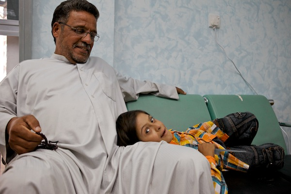 A photo of Hussain waiting with his daddy for his post-op heart screening in Najaf, Iraq.