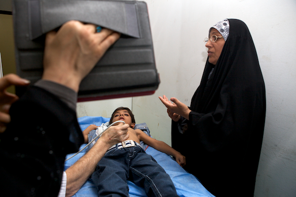 A photo of Hassin's grandmother praying over him as he watches Toy Story on an iPad and receives an echocardiogram.