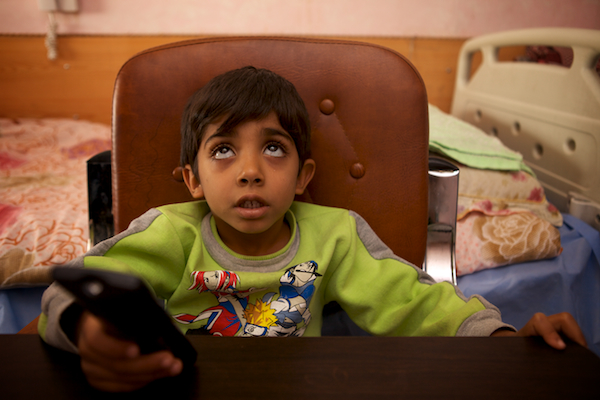 A photo of Hassin watching TV in his hospital room in Najaf, Iraq.
