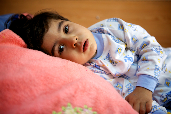A photo of little Zahraa laying on her hospital bed recovering in Najaf, Iraq.