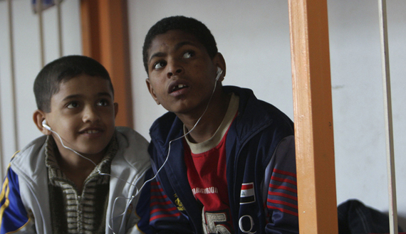 Orphans in Sadr City share a pair of headphones