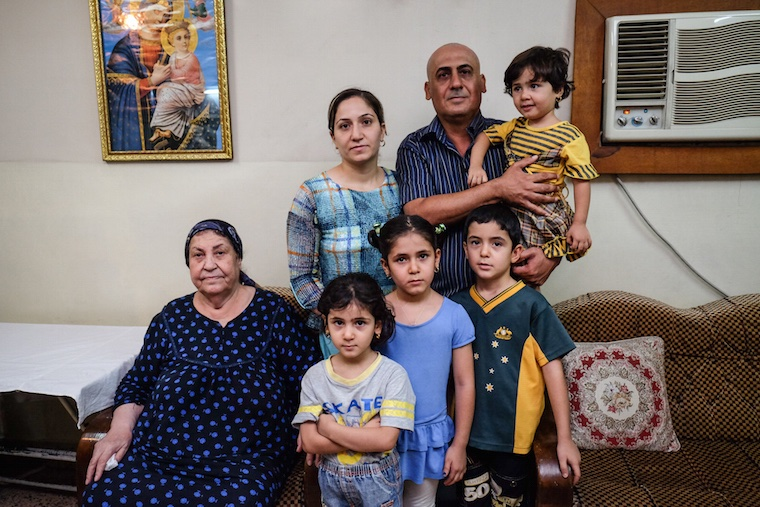 Isaac and his family pictured in their living room in Baghdad