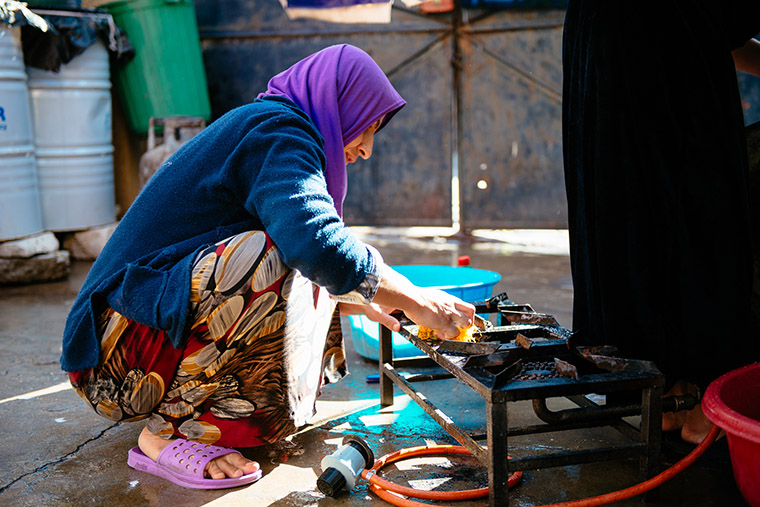 An IDP woman cleans the stove in her outdoor kitchen