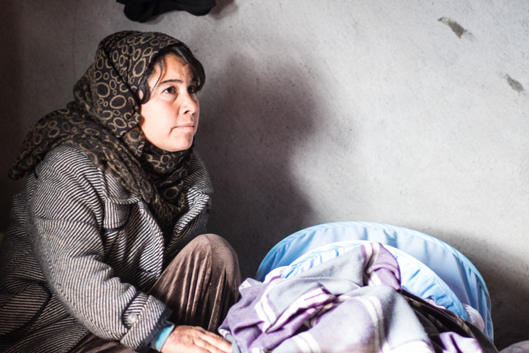 Sozan, a displaced Yezidi in Kurdistan, kneels beside her new baby.