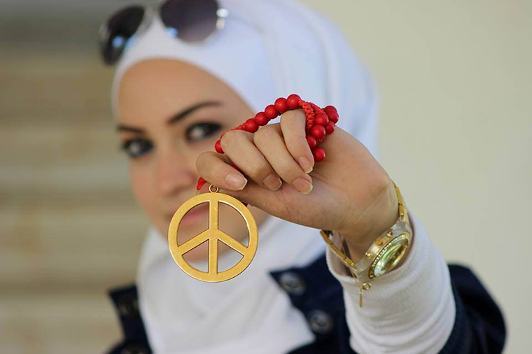 Young Syrian woman holding a peace sign.