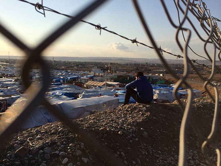 A man gazes towards Kawergosk refugee camp, Erbil governorate, Kurdistan region of Iraq.