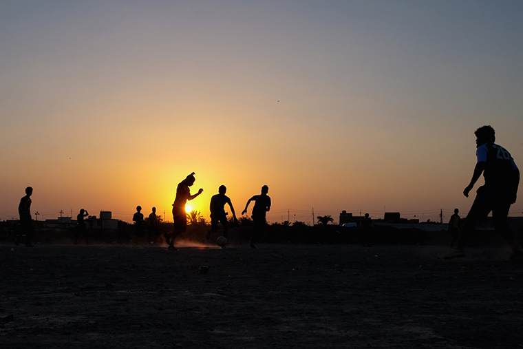 Young men in Nasiriyah play soccer, as the sun sets behind them.