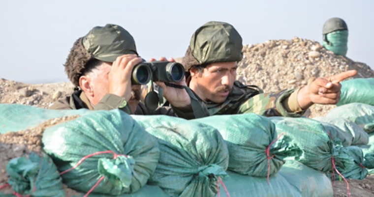 Kurdish fighters check on extremist activities on the frontline in Kharabaroot.
