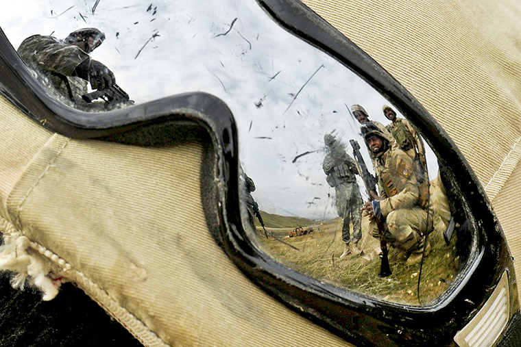 An Iraqi soldier's goggles catch the reflection of U.S. Army Staff Sgt.