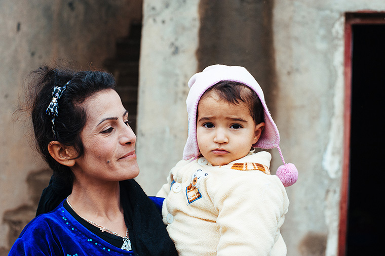 A woman displaced by violence in Iraq, looks affectionately at her small child.