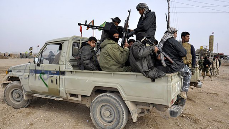 Armed Shia militia volunteers fill the back of a pickup truck.