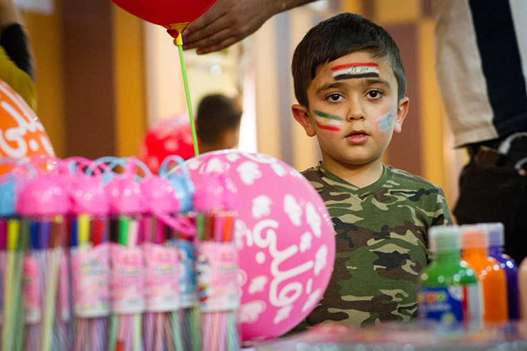 A young boy attends an Easter party, hosted by a local Assyrian community, dressed in military fatigues.