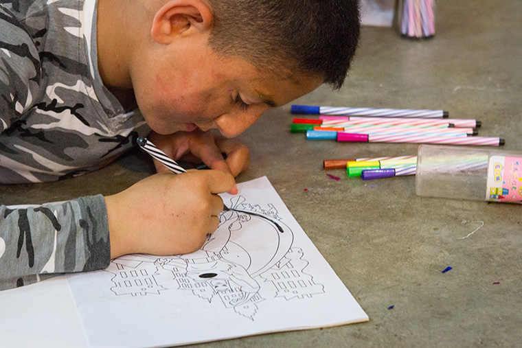 A young boy colours a superhero while attending an Easter party sponsored by a local Assyrian church.