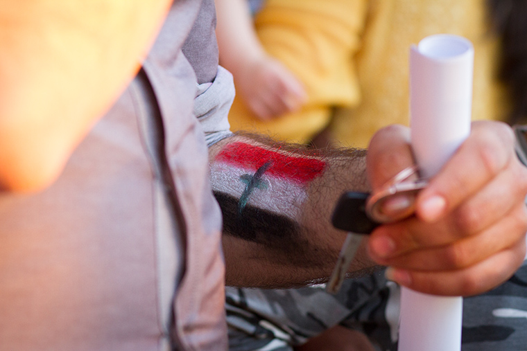 A parent made use of the face paint station to mark his forearm with a flag of his own making, featuring a cross at it's center.