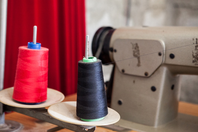 An industrial sewing machine sits at the ready, with large cones of thread.
