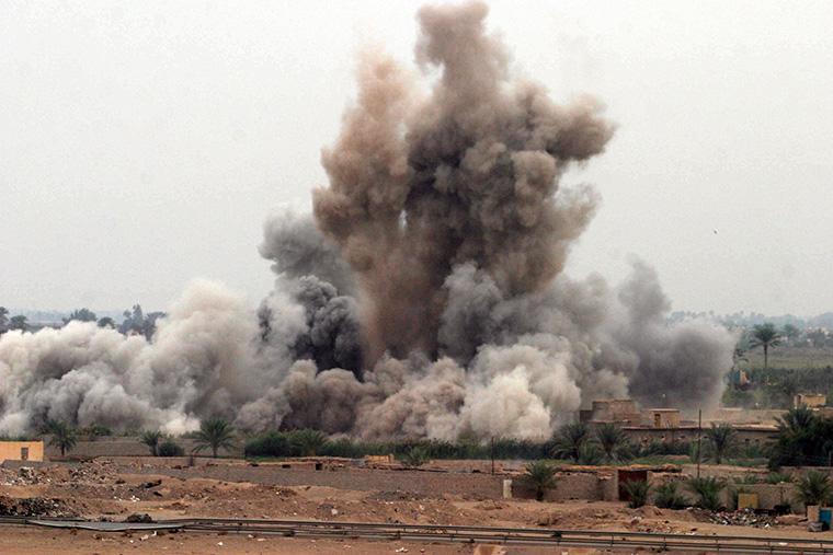 A cloud of dirt flies through the air, propelled by an explosion in Fallujah, Iraq.